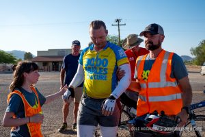 Madisyn Heistand and Sean Flanagan help Rob get to a chair to rest after racing through the desert.