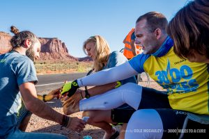 Chris Clemens and Kim Godawa massage and bandage Rob's feet in Monument Valley.